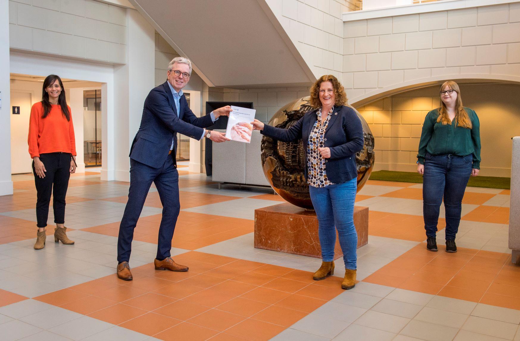 Ernst van Koesveld, directeur-generaal Langdurige Zorg bij VWS, ontvangt het rapport van Liesbeth Hoogendijk en mantelzorgers Vianne Spang en Marise Schot.